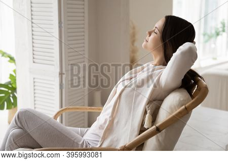 Millennial Woman Traveler Napping In Cozy Chair At Hotel Suite