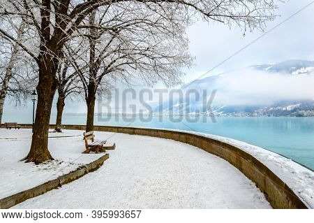 Zell Am See In Winter. Esplanade Along Lake Zell, Snow, Frozen Trees And Misty Mountain In Alpine To