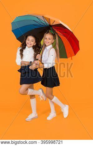Autumn Style. Happy Small Girls Holding Rainbow Style Umbrella On Yellow Background. Little Children