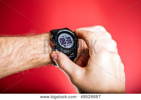 Male runner ready to run with sport watch. Taking puls or checking gps position wristwatch. Man and fitness exercising concept on red background poster