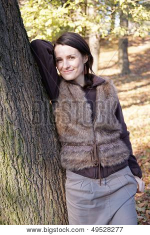 Autumn woman leaning tree