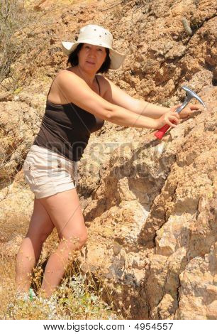 Senior woman geologist tap a rock formation with a hammer poster