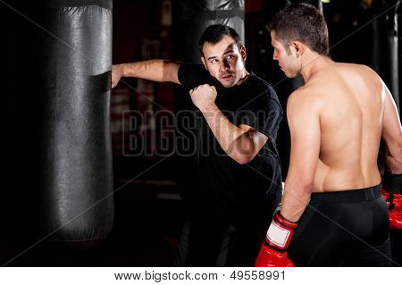 Boxer and coach training at a gym