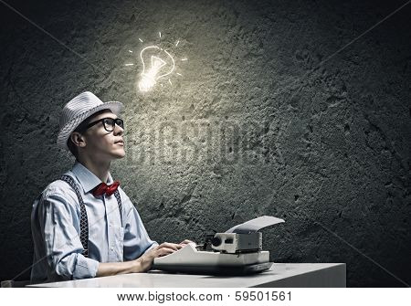 Young funny man in glasses writing on typewriter