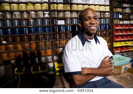 Male worker sitting in front of colored inks in print shop