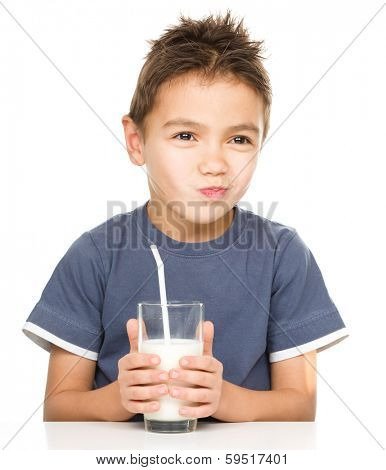 Sad little boy with a glass of milk, isolated over white