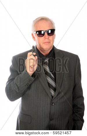 A very good looking well dressed business man in a suit brandishes a small pistol while wearing dark sunglasses. Isolated on white with room for your text. He could be a CIA Mole or Mob Lackey.