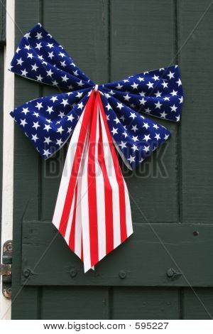 A Patriotic Ribbon is Displayed on the Green Shutter of a House. poster