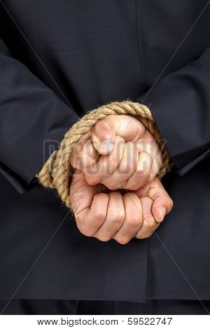 Close up of tied hands of businessman. Concept of slavery and hard work