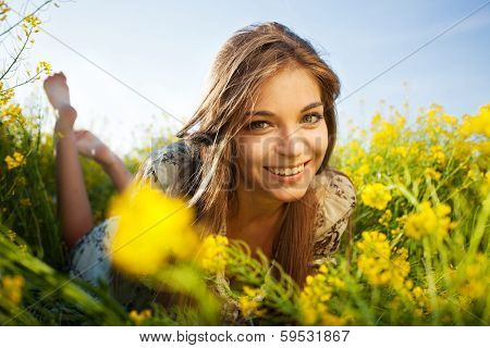 Happy Girl Lies Among Yellow Wildflowers