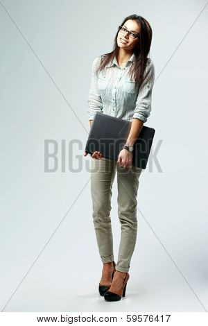 Full-length portrait of a young thoughtful businesswoman holding laptop on gray background
