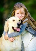 Little girl embraces her golden retriever in the summer park poster