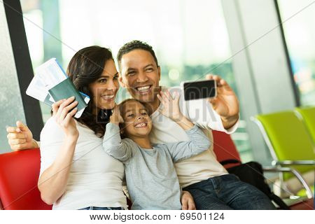 happy family at airport taking self portrait with smart phone at airport