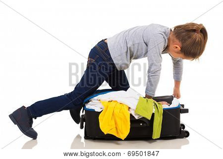 young girl kneeing on suitcase trying to zip it up