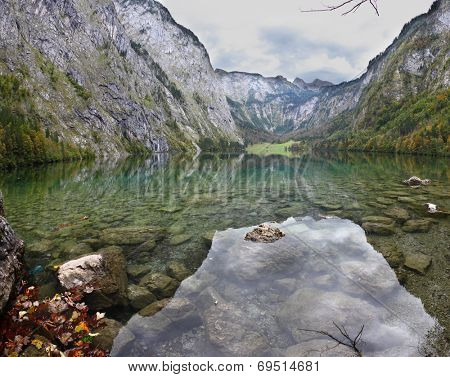 Magic reflection in German lake Koenigssee. Cloudy day on the lake. Clouds and mountains reflected in the mirrored surface of the water