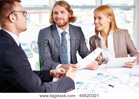 Two business partners listening to interviewee in office