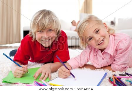 Smiling Children Drawing Lying On The Floor