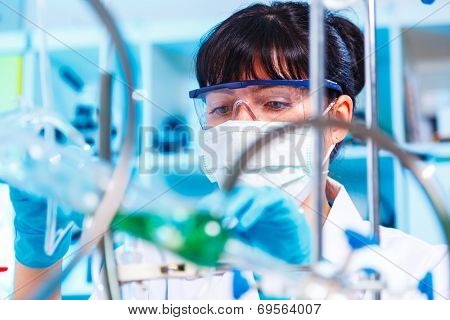 Female lab doing an experiment on the synthesis of the artificial protein