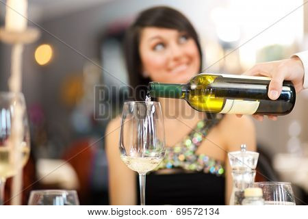 Waiter pouring white wine to a beautiful woman