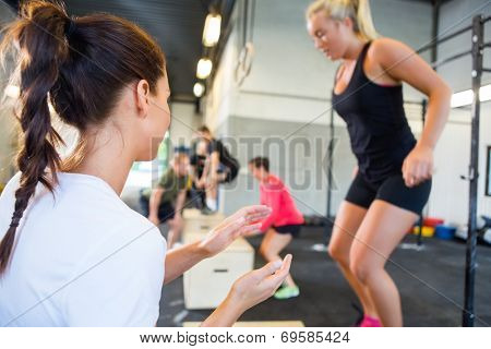 Female gym instructor encouraging athlete in box jumping at gym
