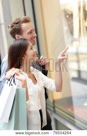 Woman and man shopping in Hong Kong Central. Couple looking at shop windows holding shopping bags. Urban mixed race Asian Chinese woman shopper and Caucasian man smiling happy living in city.