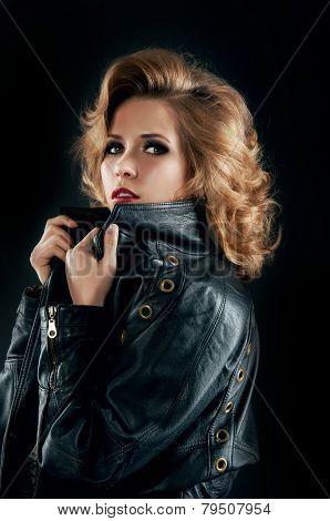 Studio portrait of blonde woman in leather biker jacket.Rock style. poster