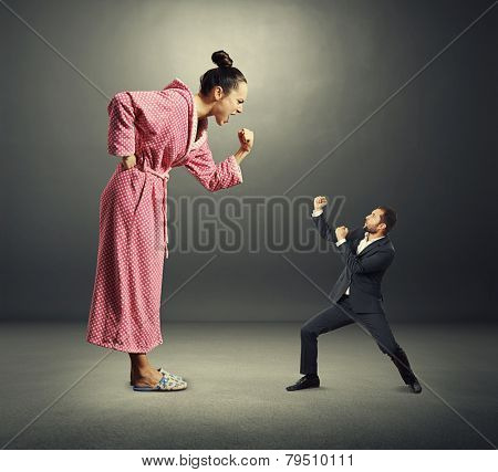quarrel between angry wife and small henpecked husband over dark background