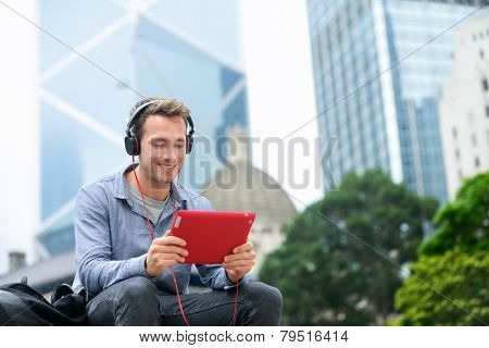 Man talking on tablet pc having video chat conversation in sitting outside using app on 4g wireless device wearing headphones. Casual young urban professional male in his late 20s. Hong Kong. poster