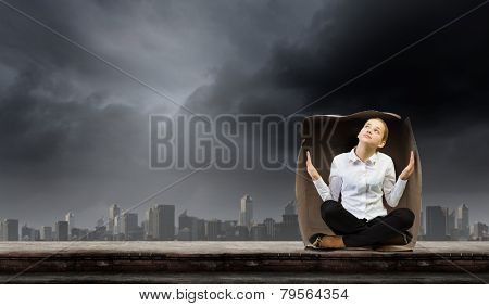 Young businesswoman sitting in carton box and feeling uncomfortable poster