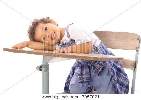 adorable little boy sitting in a desk