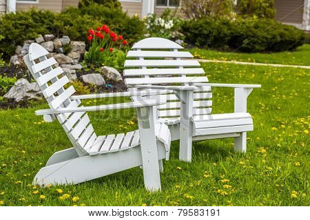 Round back Adirondack chairs fondly know as a moon chair in front of a home and flower beds.