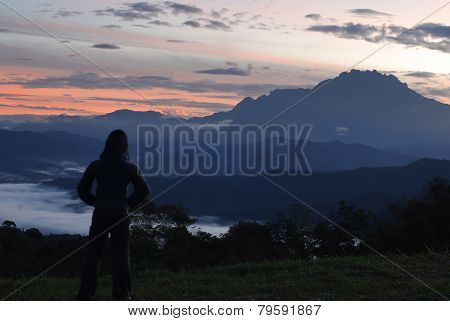 Sillhouette Of A Woman Enjoying The Early Dawn With Mount Kinabalu As Background