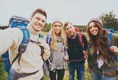 adventure, travel, tourism, hike and people concept - group of smiling friends with backpacks making selfie outdoors poster