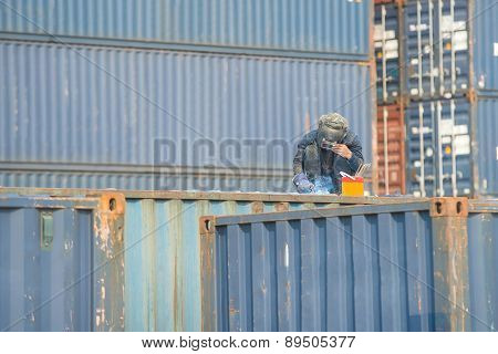 Worker Welding To Repair Container Box In Port