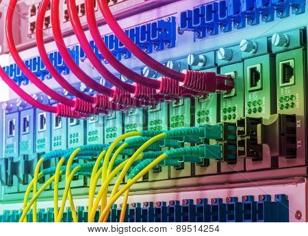 Fiber Optic cables connected to an optic ports and UTP Network cables connected to an Fast/Giga Ethernet ports poster