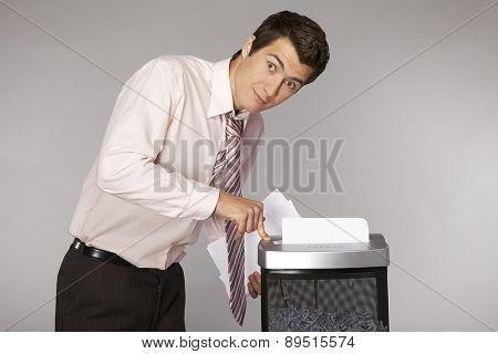 Young caucasian businessman shredding documents
