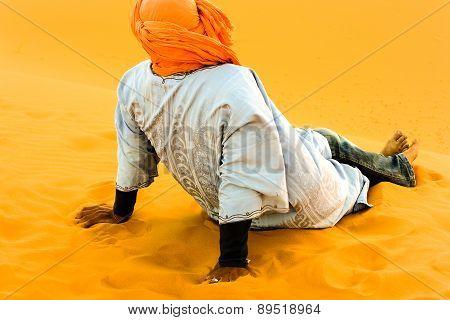 Camel driver resting on sand dune after work