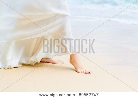 Beautiful Young Bride In A White Wedding Dress Walking On A Tropical Sandy Beach. Feet Close-up.