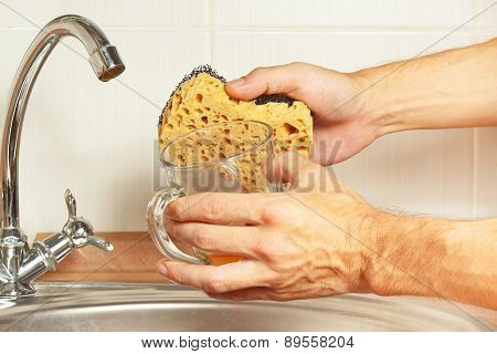 Hands with sponge and dirty glass over the sink in kitchen
