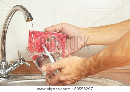 Hands with sponge wash the glass over the sink in kitchen