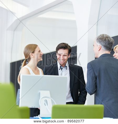 Happy group of business people having smalltalk in office