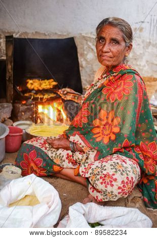KAMALAPURAM, INDIA - 02 FEBRUARY 2015: Elderly Indian woman in traditional clothes frying vegatables on a market close to Hampi