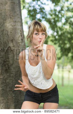 Pretty young woman making a shushing gesture