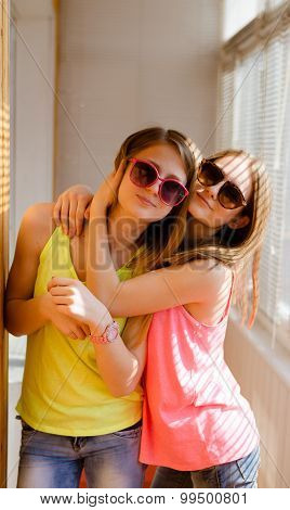 Two happy pretty teenage girls in sunglasses hugging