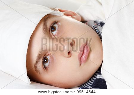 Boy with the compress preparing for treatment procedures