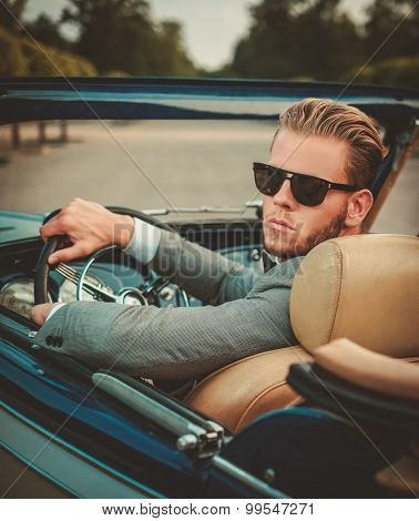 Confident wealthy young man behind classic convertible steering wheel