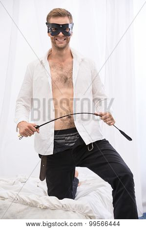 Handsome guy with whip BDSM in the leather mask