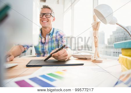 Smiling casual designer using computer and digitizer in the office