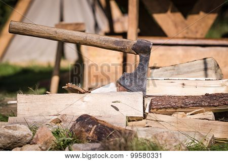Axe impaled in log and fragments