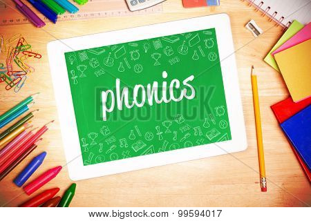 The word phonics and school wallpaper against students desk with tablet pc